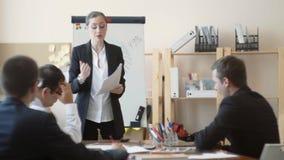Een meisje in een pak houdt belangrijke rapporten in haar handen, is zij ontevreden met hen en berispt haar werknemers stock video