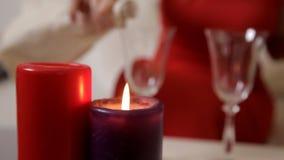Een meisje in een rode kleding zit bij een lijst door kaarslicht en drinkt champagne van een glas stock footage