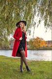 Een meisje in een rode laag en hoedenplanken onder de takken van een wilg op de bank van de rivier van het meer Royalty-vrije Stock Fotografie