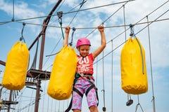 Een meisje in een roze helm overwint hindernissen op de kabelwagen in een extreem park royalty-vrije stock afbeeldingen