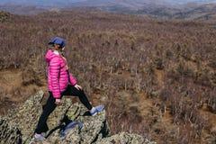 Een meisje in een roze jasje bevindt zich op een hoge berg Royalty-vrije Stock Foto's