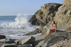 Een meisje in roze zwemmend kostuum op het rotsachtige strand Stock Foto's