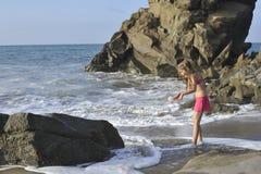 Een meisje in roze zwemmend kostuum op het rotsachtige strand Stock Foto