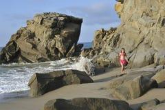 Een meisje in roze zwemmend kostuum op het rotsachtige strand Stock Afbeelding