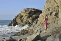 Een meisje in roze zwemmend kostuum op het rotsachtige strand Stock Fotografie