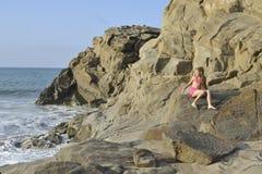 Een meisje in roze zwemmend kostuum op het rotsachtige strand Royalty-vrije Stock Afbeelding