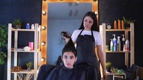 Een meisje in een schoonheidssalon met een kapper Het concept haarverzorging in de salon, keratine, haar het rechtmaken stock video