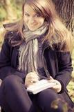Een meisje schrijft op een stootkussen in het park Stock Foto's