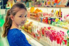 Een meisje in een snoepwinkel kiest multicolored suikergoed en lollys stock afbeeldingen