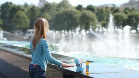 Een meisje speelt met water dichtbij een fontein stock video