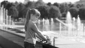 Een meisje speelt met water dichtbij een fontein stock videobeelden