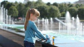 Een meisje speelt met water dichtbij een fontein stock footage