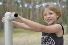 Een meisje speelt op de speelplaats Stock Foto's