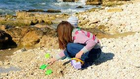 Een meisje speelt op het strand met een kleine jongen stock videobeelden