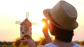 Een meisje in een strohoed bevindt zich op een zonnebloemgebied en houdt een stuk speelgoed molen in de handen tegen de zonsonder stock video