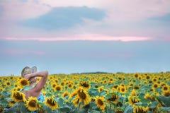 Een meisje in een strohoed op het gebied van zonnebloemen stock afbeelding