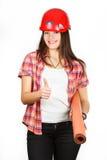 Een meisje toont in de helm van bouwer, aan dat allen goed zullen zijn Royalty-vrije Stock Afbeeldingen