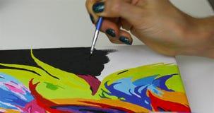 Een meisje trekt een borstel met zwarte verf op canvas stock video