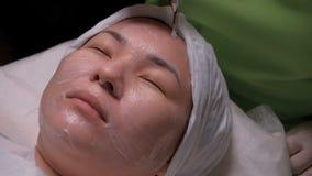 Een meisje van Aziatische verschijning op een procedure van disincrustation in het de kosmetiekbureau Vrouwelijk gezicht op het g stock footage