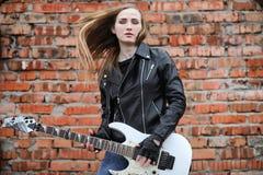 Een meisje van de rotsmusicus in een leerjasje met een gitaar Stock Foto