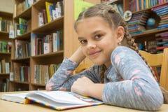Een meisje van tien jaar brengt tijd in de bibliotheek door stock foto