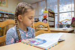 Een meisje van tien jaar oud leest een boek in de bibliotheek stock foto's