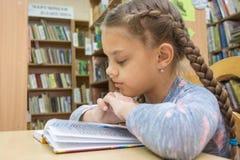 Een meisje van tien jaar oud leest een boek in de lezingsruimte royalty-vrije stock afbeeldingen