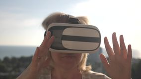 Een meisje in virtuele werkelijkheidsglazen op het dak van het huis bij zonsondergang in de zon Vital Life Concept stock video