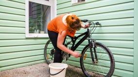 Een meisje wast een fiets stock video