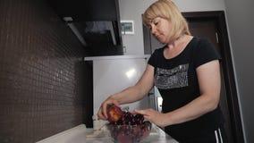 Een meisje wast fruit en legt hen op een plaat in haar keuken stock footage