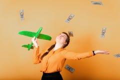 Een meisje werpt dollars aan de kant en houdt een groen vliegtuig in haar hand, een teken van vrijheid en financiële onafhankeli stock fotografie