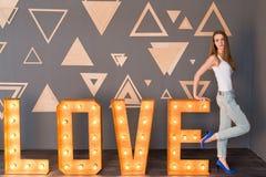 Een meisje in wit hemd en blauw denim met gaten die op een houten het van letters voorzien Liefde met gloeilampen leunen Royalty-vrije Stock Afbeelding