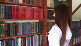 Een meisje in een witte blouse en glazen in de bibliotheek kiest boeken stock footage