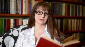 Een meisje in een witte blouse en glazen in de bibliotheek kiest boeken stock videobeelden