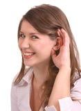 Een meisje in witte blouse luistert. Stock Fotografie