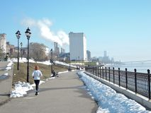 Een meisje in witte eenvormige sporten is bezig geweest met het lopen, loopt zij langs de de lentekust op een de lentedag stock afbeelding