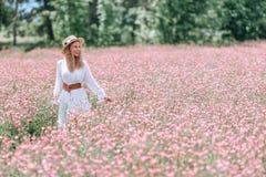 Een meisje in een witte kleding met stippen en een hoed op een bloeiend gebied van esparcette stock afbeeldingen