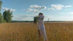Een meisje in een witte kleding werpt omhoog wilde bloemen en loopt langs het tarwegebied stock video