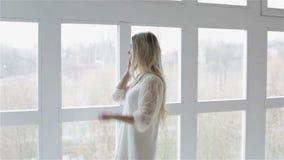 Een meisje in witte manierkleding typt aantal op mobiele telefoon en spreekt dichtbij venster stock footage