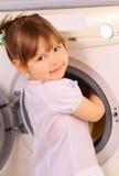 Een meisje zet handdoeken in de wasmachine Stock Afbeeldingen