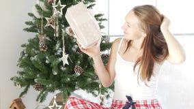 Een meisje zit door het venster en beschouwt als haar Kerstmis huidig stock footage