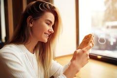 Een meisje zit in een koffie en gebruikt een smartphone Stock Foto