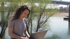 Een meisje zit met laptop op de rivierbank Een de lente zonnige dag op de waterkant Jonge vrouw bij het water met laptop stock footage