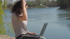 Een meisje zit met laptop op de rivierbank Een de lente zonnige dag op de waterkant Jonge vrouw bij het water met laptop stock videobeelden