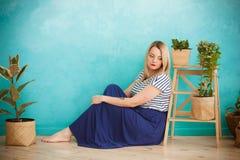 Een meisje zit naast binneninstallaties Stock Foto