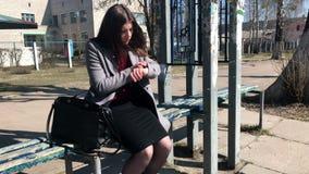 Een meisje zit op een bank bij een bushalte en bekijkt haar horloge terwijl het wachten op vervoer stock videobeelden