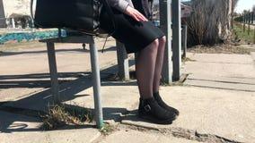 Een meisje zit op een bank bij een bushalte en schudt haar benen in anticiperen stock videobeelden