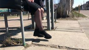 Een meisje zit op een bank bij een bushalte en schudt haar benen in anticiperen stock video