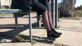 Een meisje zit op een bank bij een bushalte en schudt haar benen in anticiperen stock footage