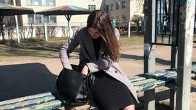 Een meisje zit op een bank bij een bushalte en zoekt iets in haar zak stock video